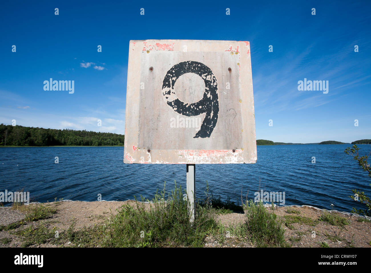 weathered old speed limit sign at harbour - Stock Image