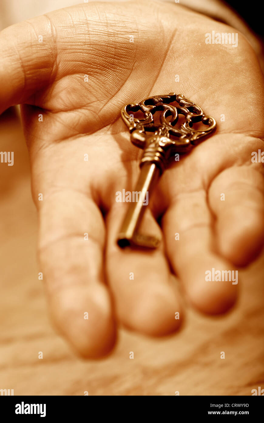 Hand with key, sepia tones  - Stock Image
