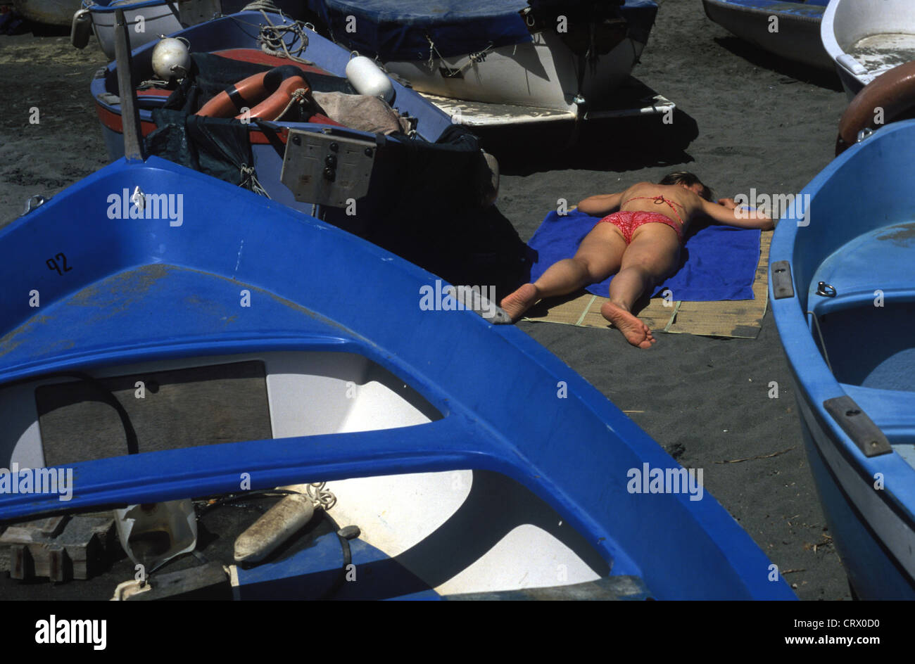 Woman lying in a confined space between boats - Stock Image