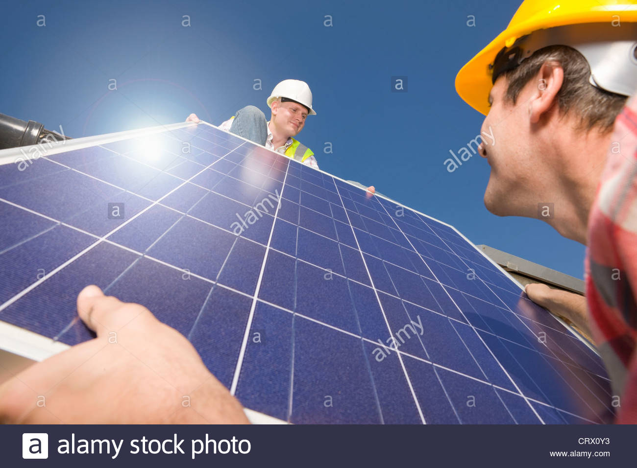 Engineers lifting solar panel onto roof - Stock Image