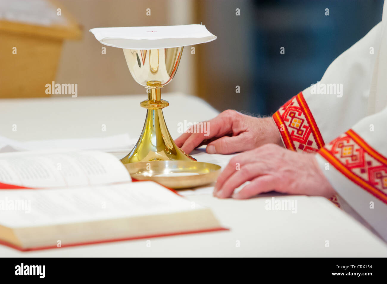 Catholic Mass and a priest holding a chalice during the religious ceremony. - Stock Image