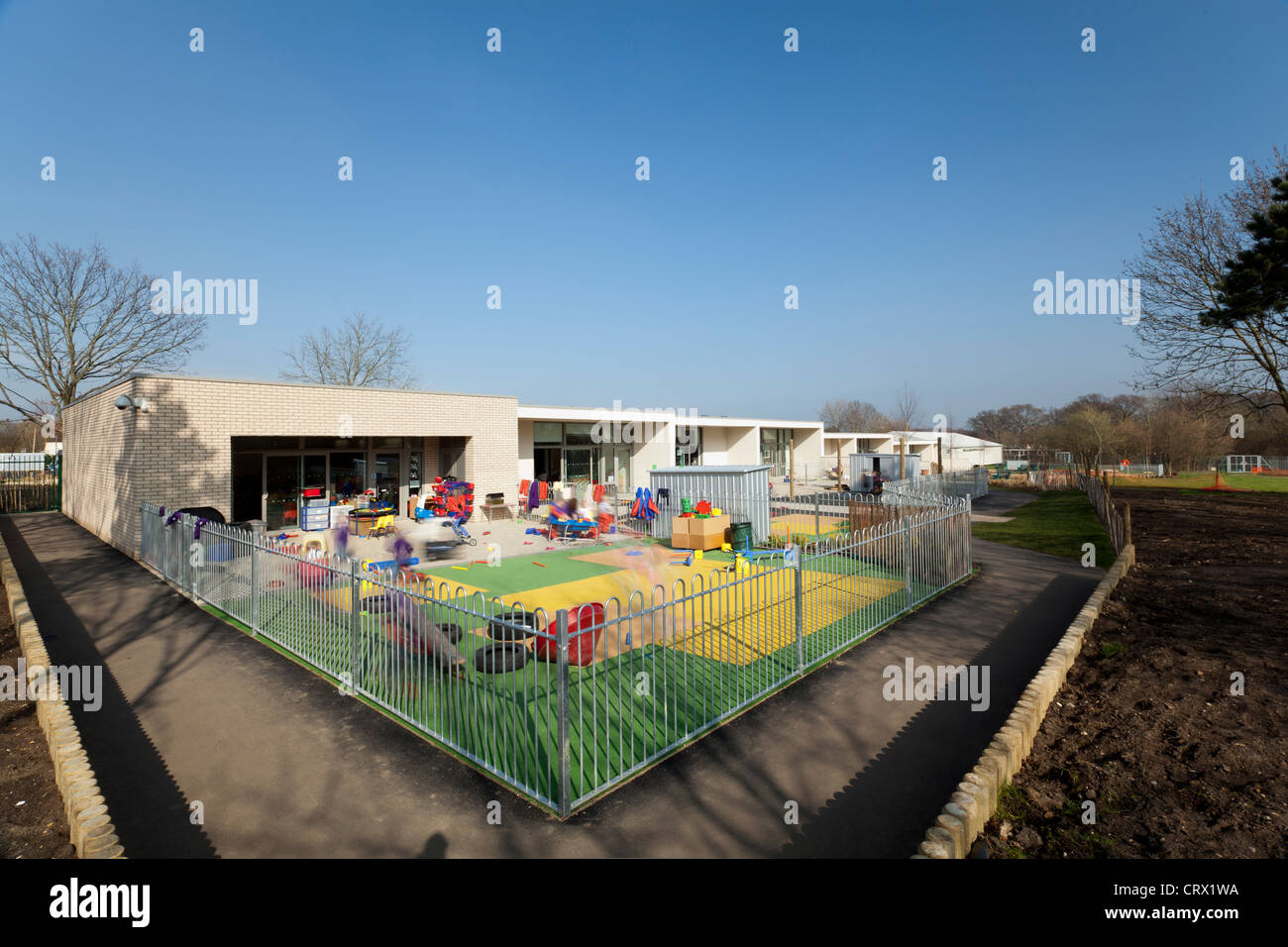 Primary school playground with blurred children playing - Stock Image