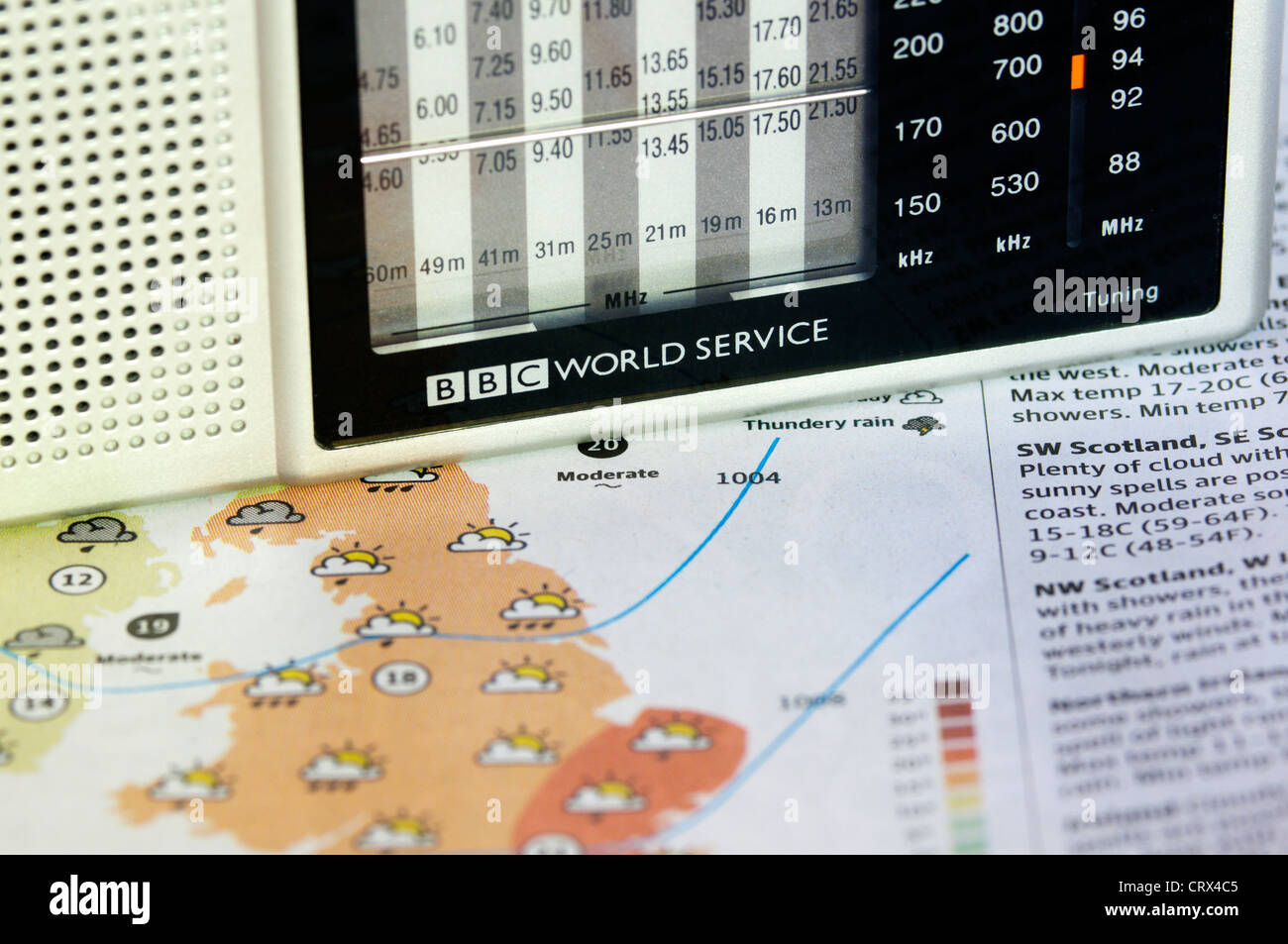 A BBC World Service radio resting on a newspaper weather map or chart. Stock Photo