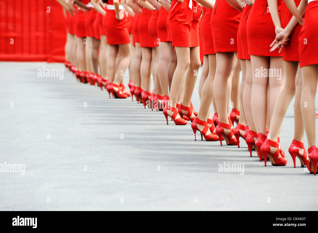 women wearing red dresses and red high-heeled shoes stand in a row - Stock Image