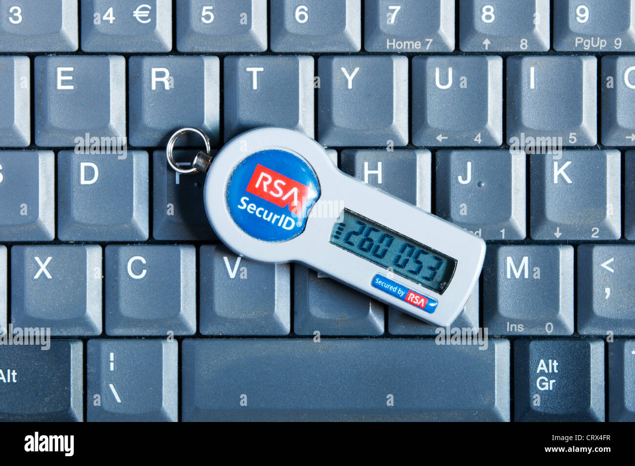 An RSA SecurID security token resting on the keyboard of a laptop computer. - Stock Image