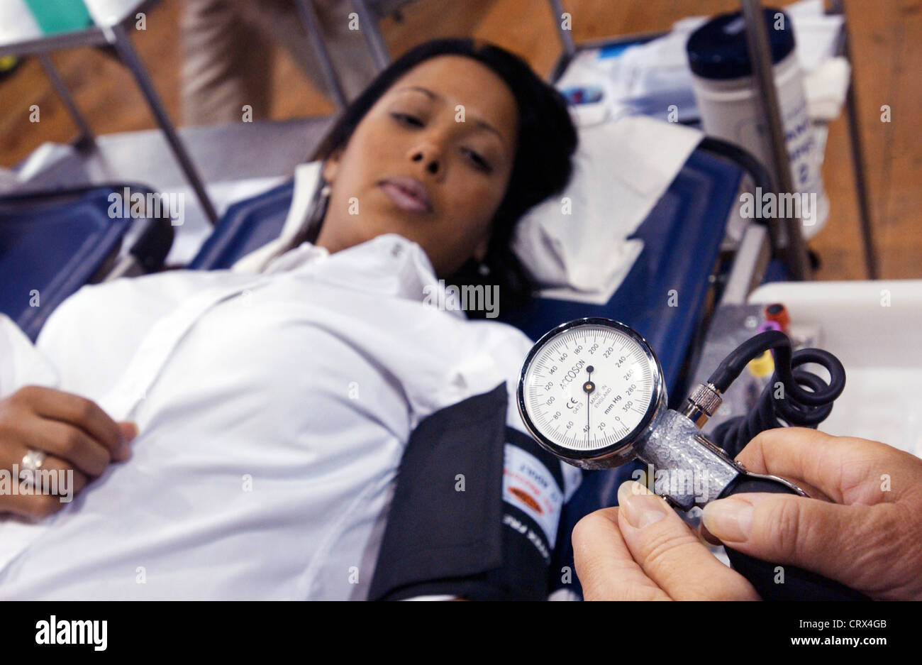 NHS National Blood Service nurse checks the blood pressure of a young female donor with the air pump of a sphygmomanometer. - Stock Image