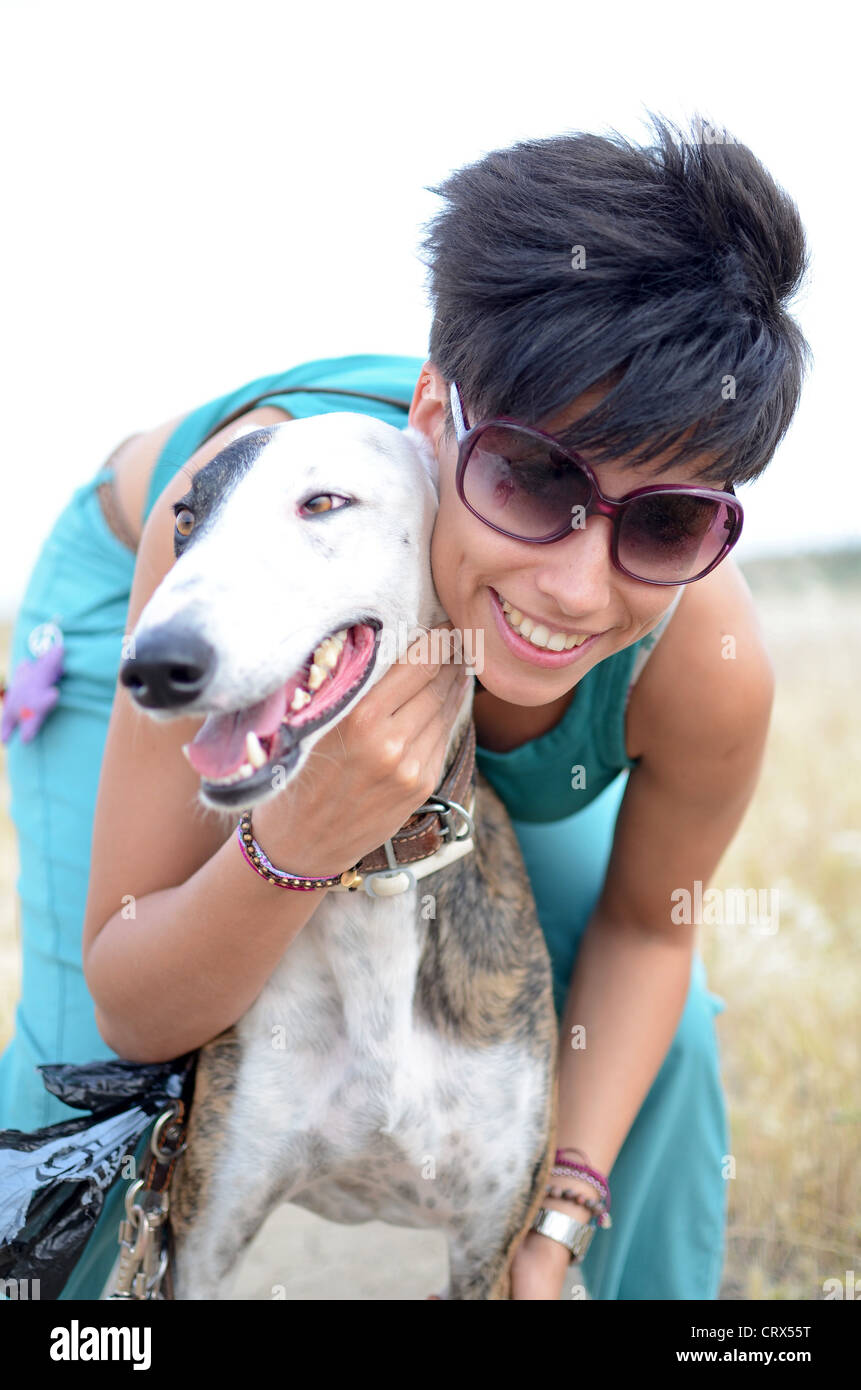 Attractive woman poses with her Spanish Greyhound in Nature - Stock Image