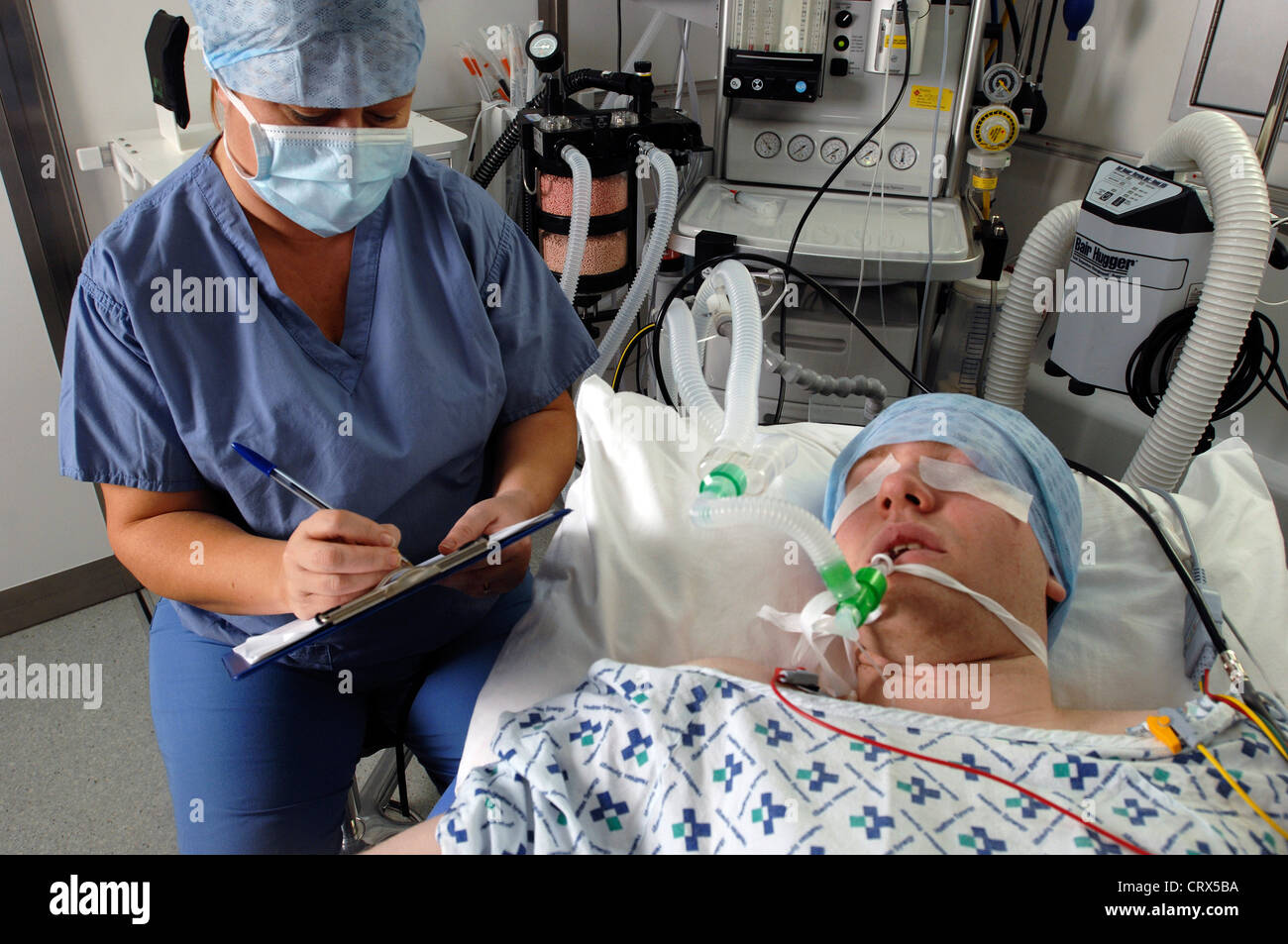 With his eyes taped, a male patient is being watched over by an anesthetist during an operation. Stock Photo