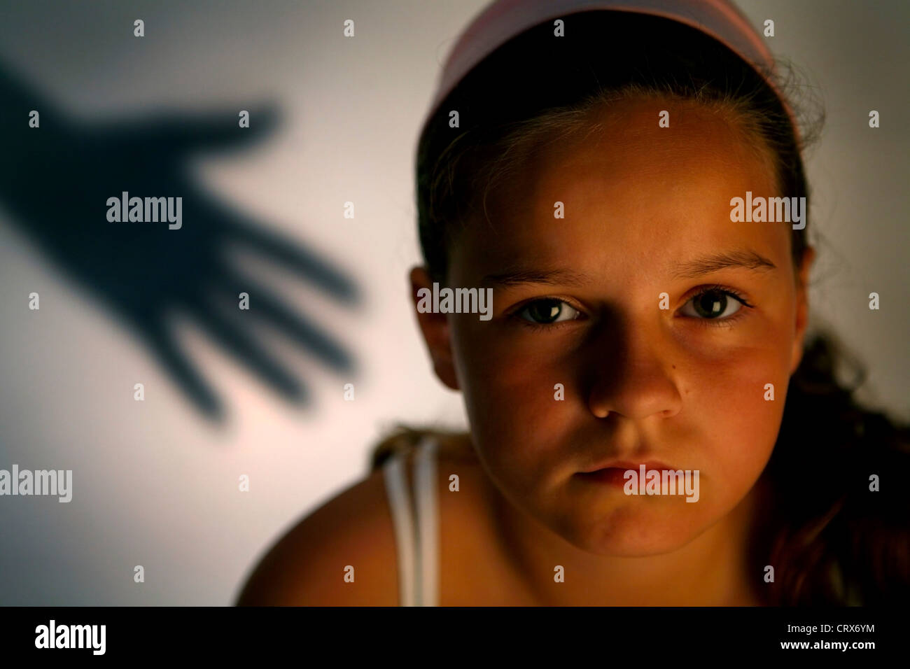 A young girl cowering away from her attacker. - Stock Image