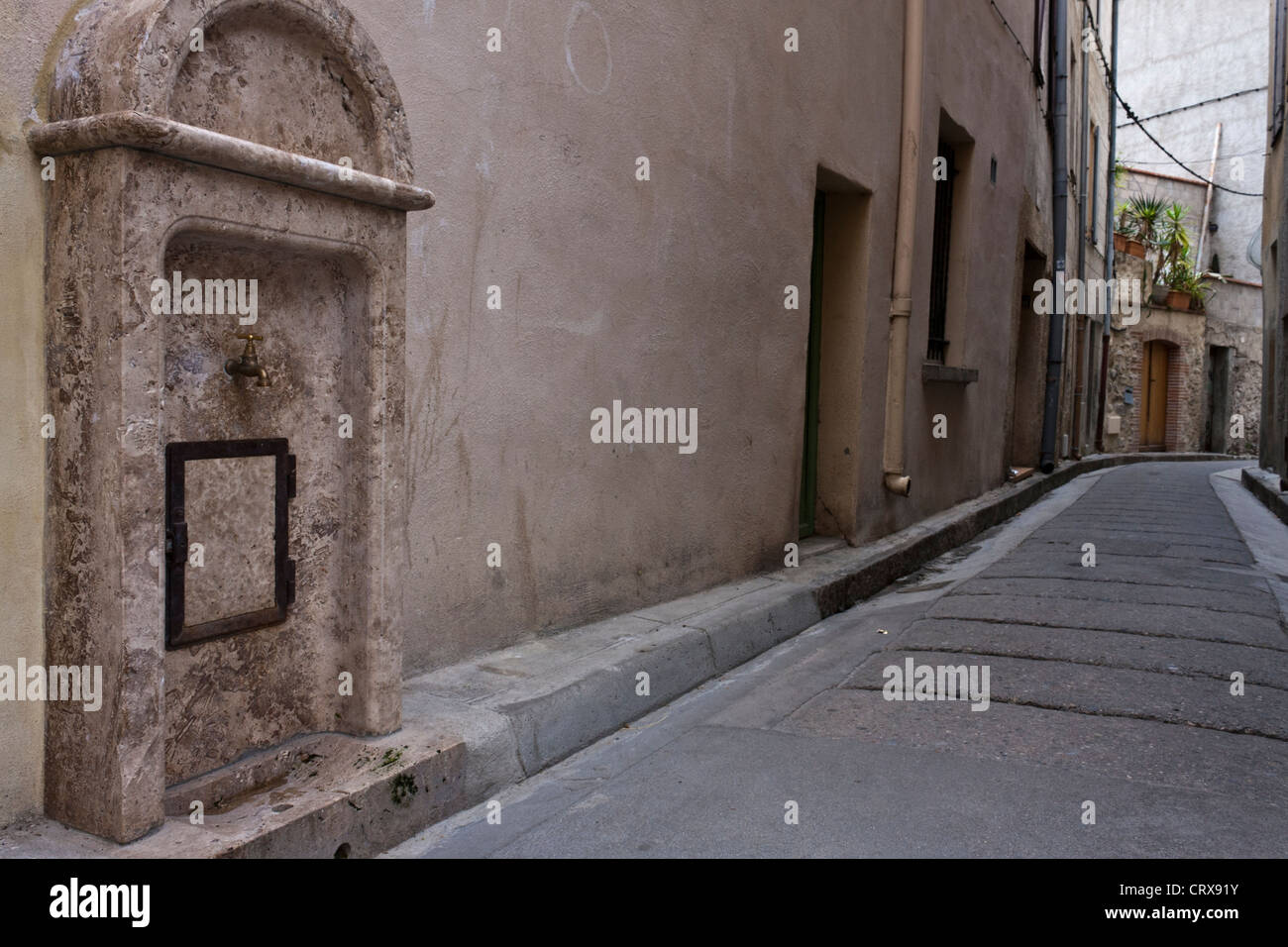 A public drinking water tap on a side street in the tourist town of Ceret, Languedoc-Roussillon, France. - Stock Image