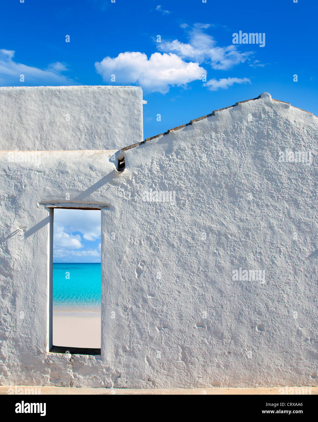 Balearic islands idyllic turquoise beach view through whitewashed house open door Stock Photo