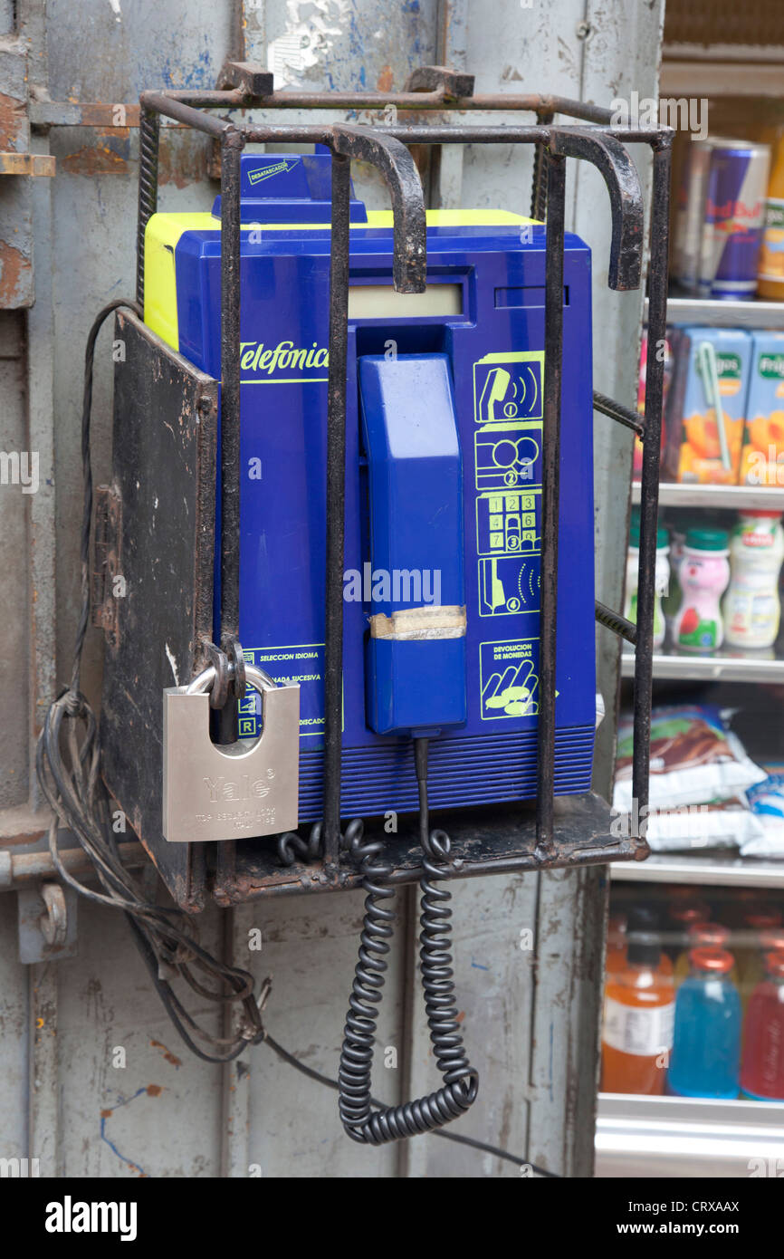 Telephone in a street of Lima outside a shop heavily secured with metal bars, cage, Lima, Peru - Stock Image
