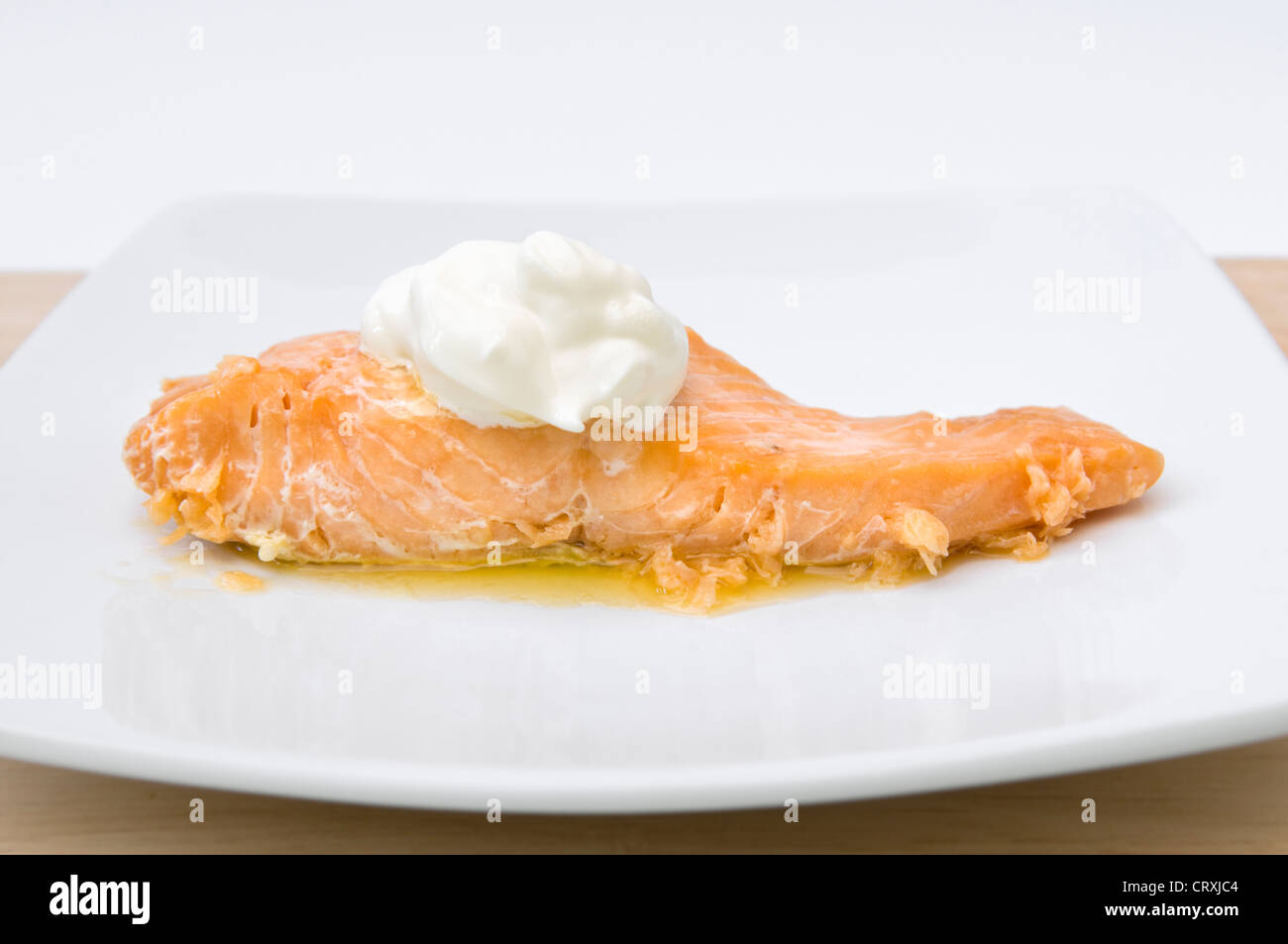 Cooked salmon with dollop of creme fraiche and melted butter on white plate - Stock Image