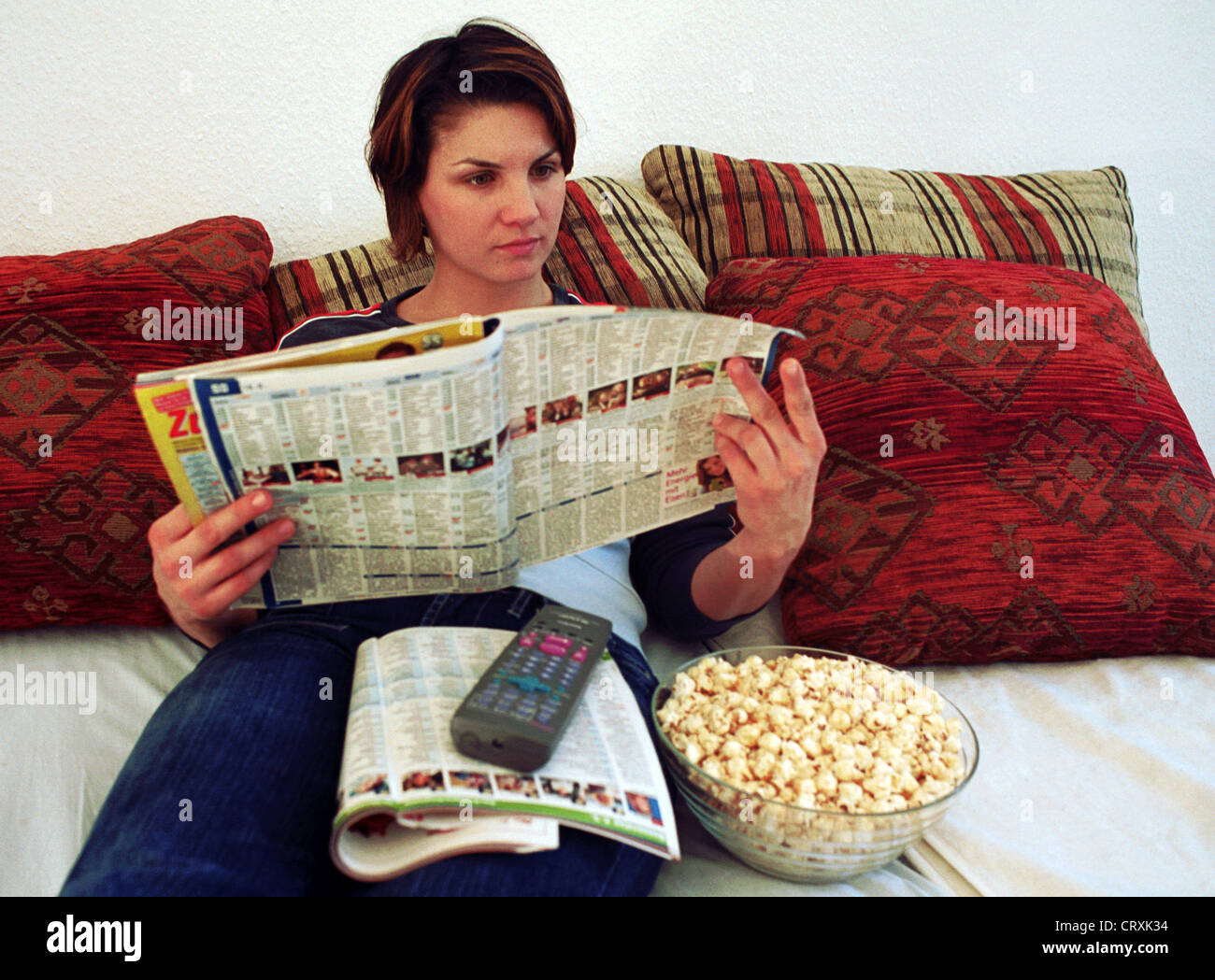 A young woman reading in the TV program - Stock Image