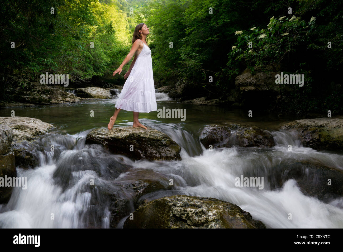 Beautiful young girl on a river in the forest charging herself with the energies of Nature - Stock Image