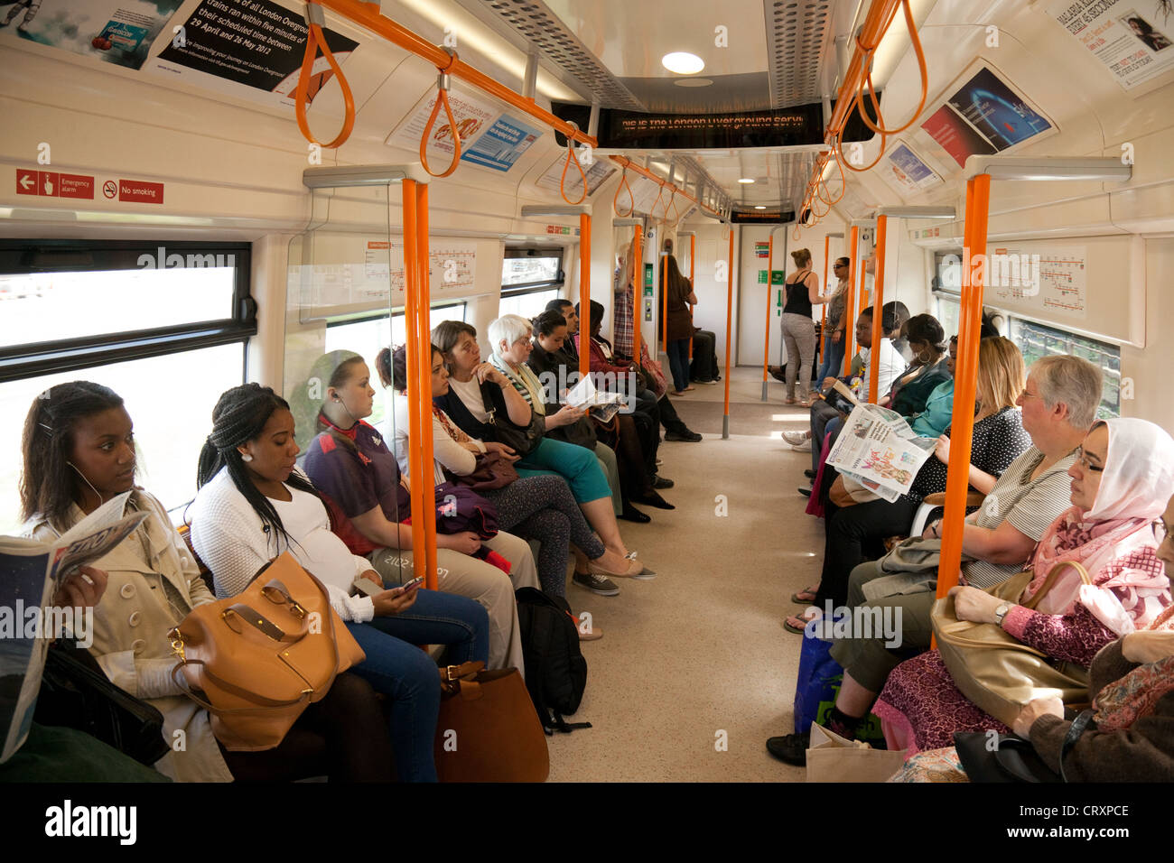 Passengers in a train carriage on the London Overground railway system, London UK - Stock Image