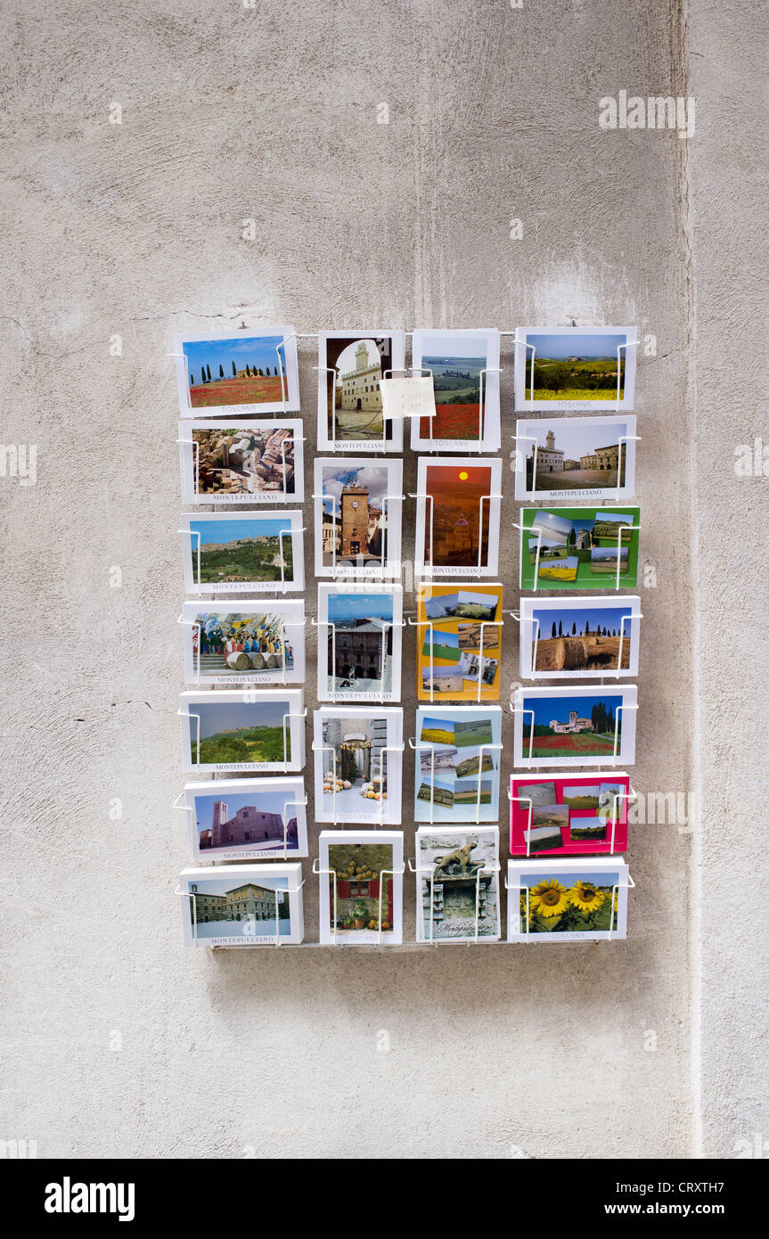 Picture post cards in a rack on the wall outside of a shop in Italy - Stock Image