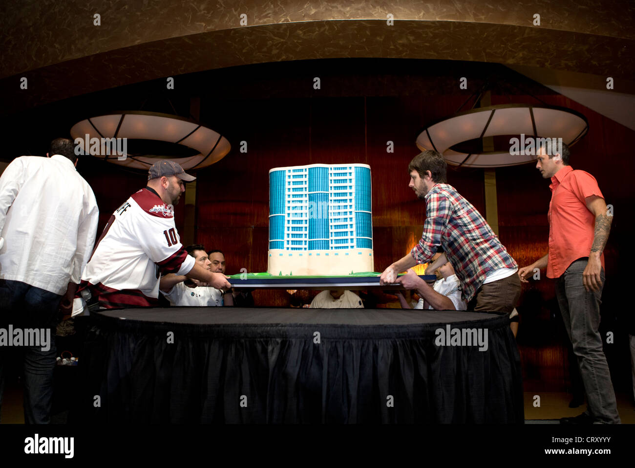 Duff Goldman and Geof Manthorne move a cake replica of the MGM at Foxwoods during the 2nd Anniversary party. - Stock Image
