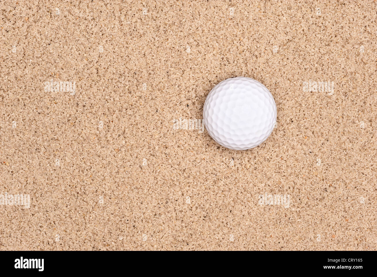 A lone golf ball in a sand trap looking top down with plenty of room for placement of copy. - Stock Image