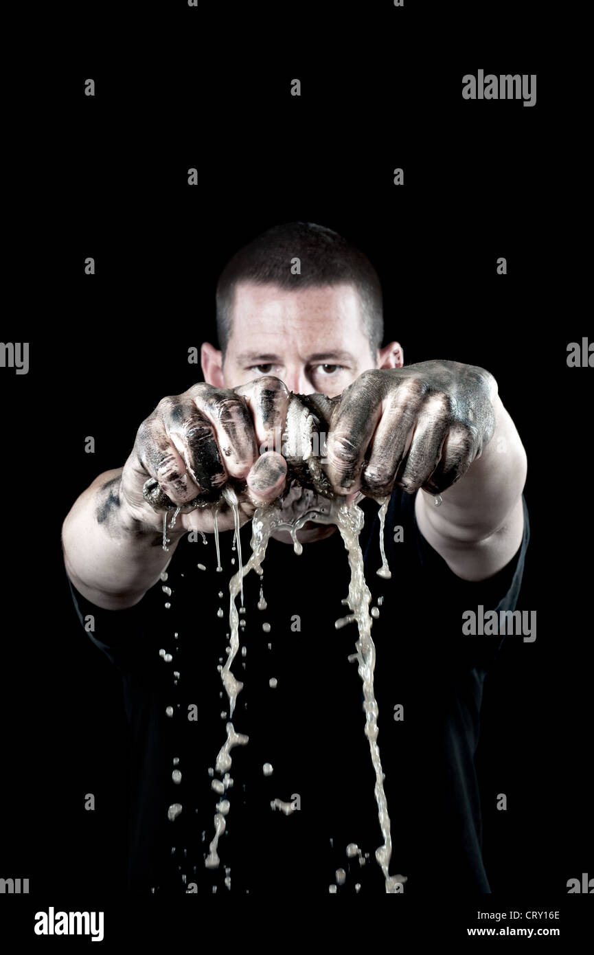 A man wrings out a dirty water soaked rag with grungy, filthy hands. Focus is on the hands and rag. - Stock Image