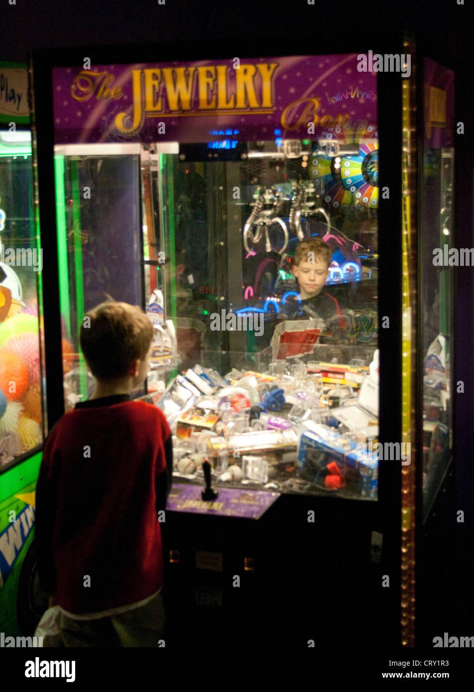 Boy age 8 playing the Jewelry Box crane machine arcade claw game. Grand Slam Amusement Center Burnsville Minnesota - Stock Image