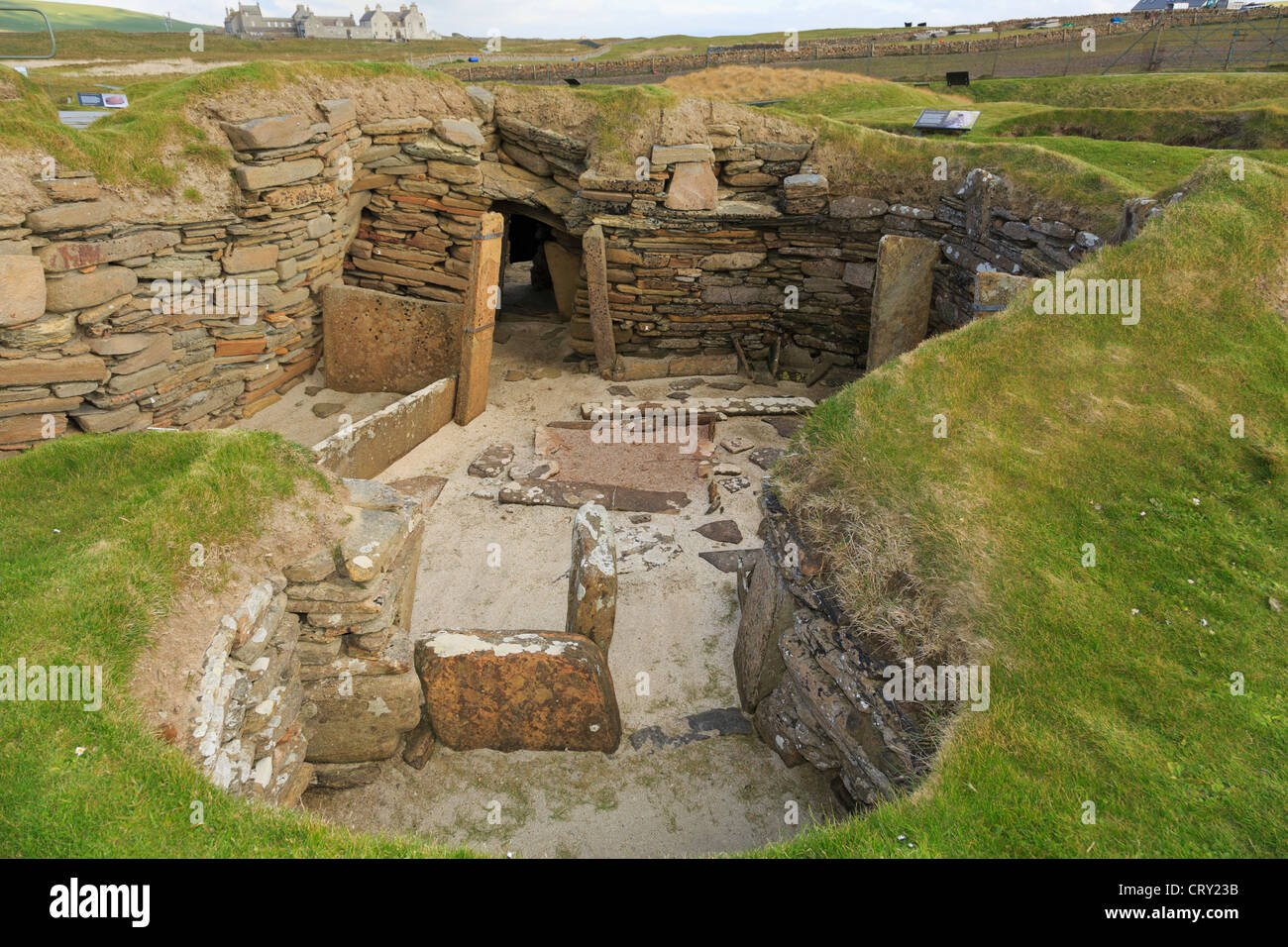 Excavations of primeval dwelling with connecting passage in prehistoric Neolithic village at Skara Brae Orkney Islands Stock Photo