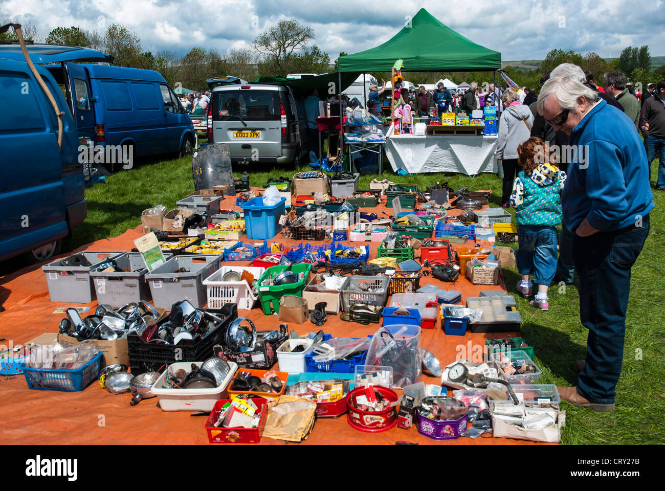 Car show market trader stall with buyers looking at merchandise ...