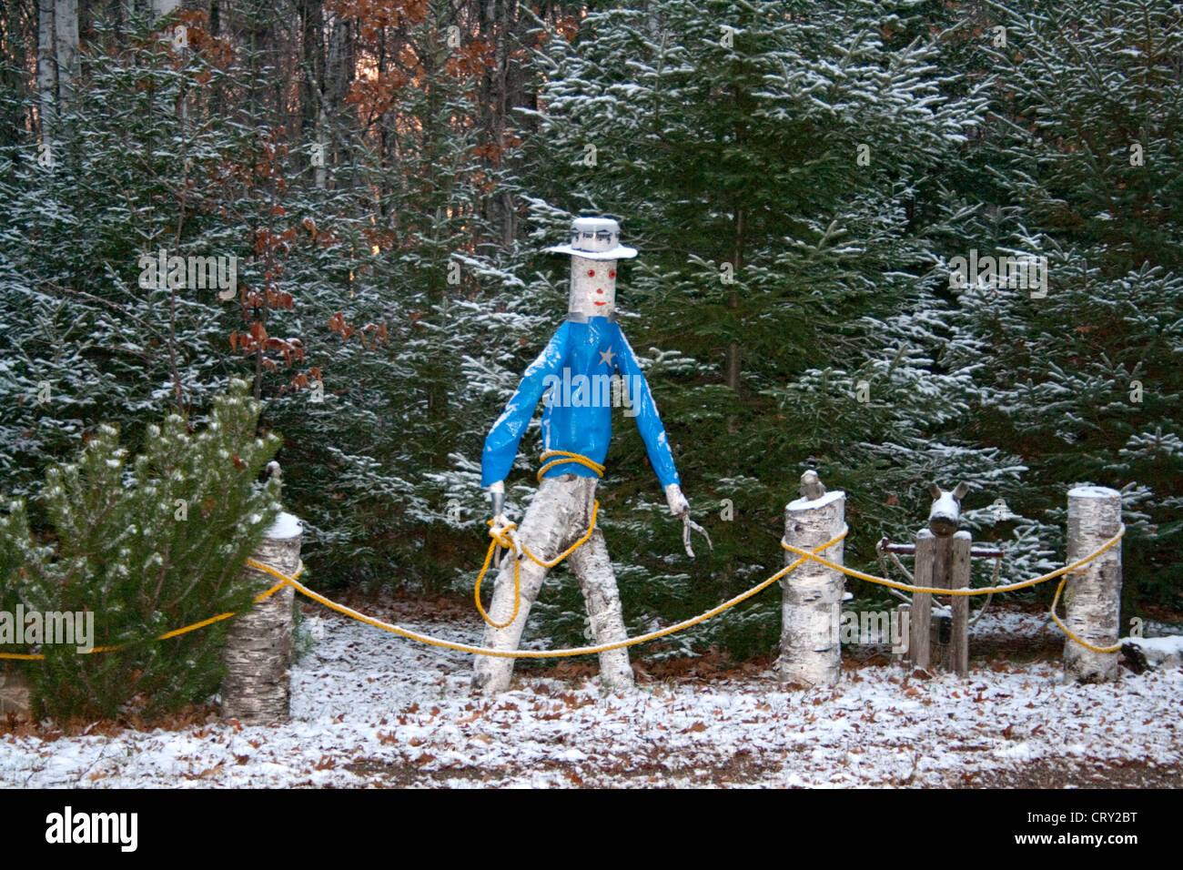 Outdoor snowy birch tree sculpture of cowboy carrying a lasso and wearing a star badge. Cable Wisconsin WI USA - Stock Image