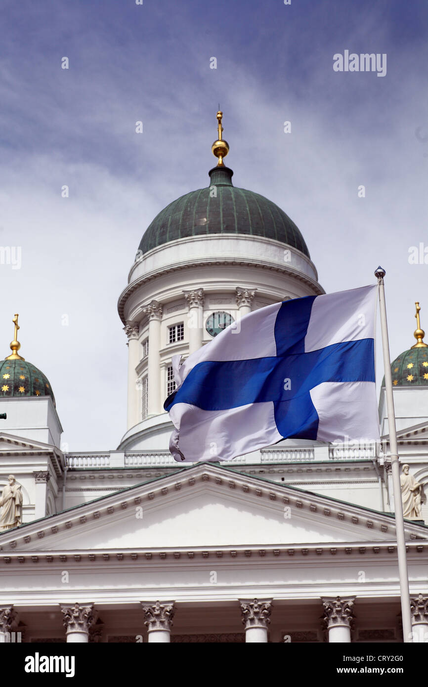 fluttering national flag of Finland against Helsinki Cathedral, most prominent building and symbol of the city Stock Photo