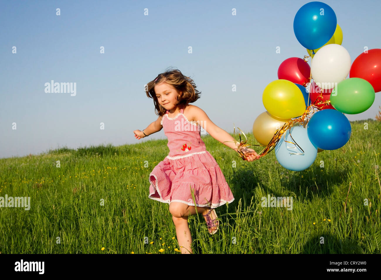 little girl runs with multicolored balloons - Stock Image