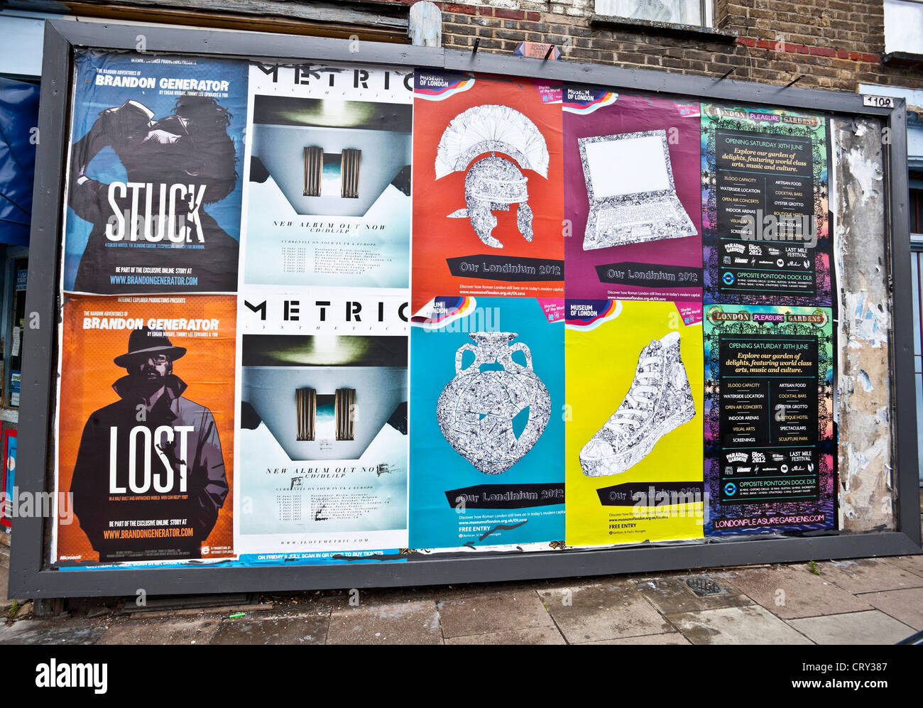 Billboard displaying colourful promotional posters, London, England, UK - Stock Image