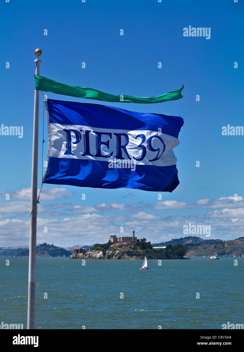 Pier 39 flag in sea breeze with Alcatraz prison island attraction and sail boat behind Embarcadero San Francisco - Stock Image