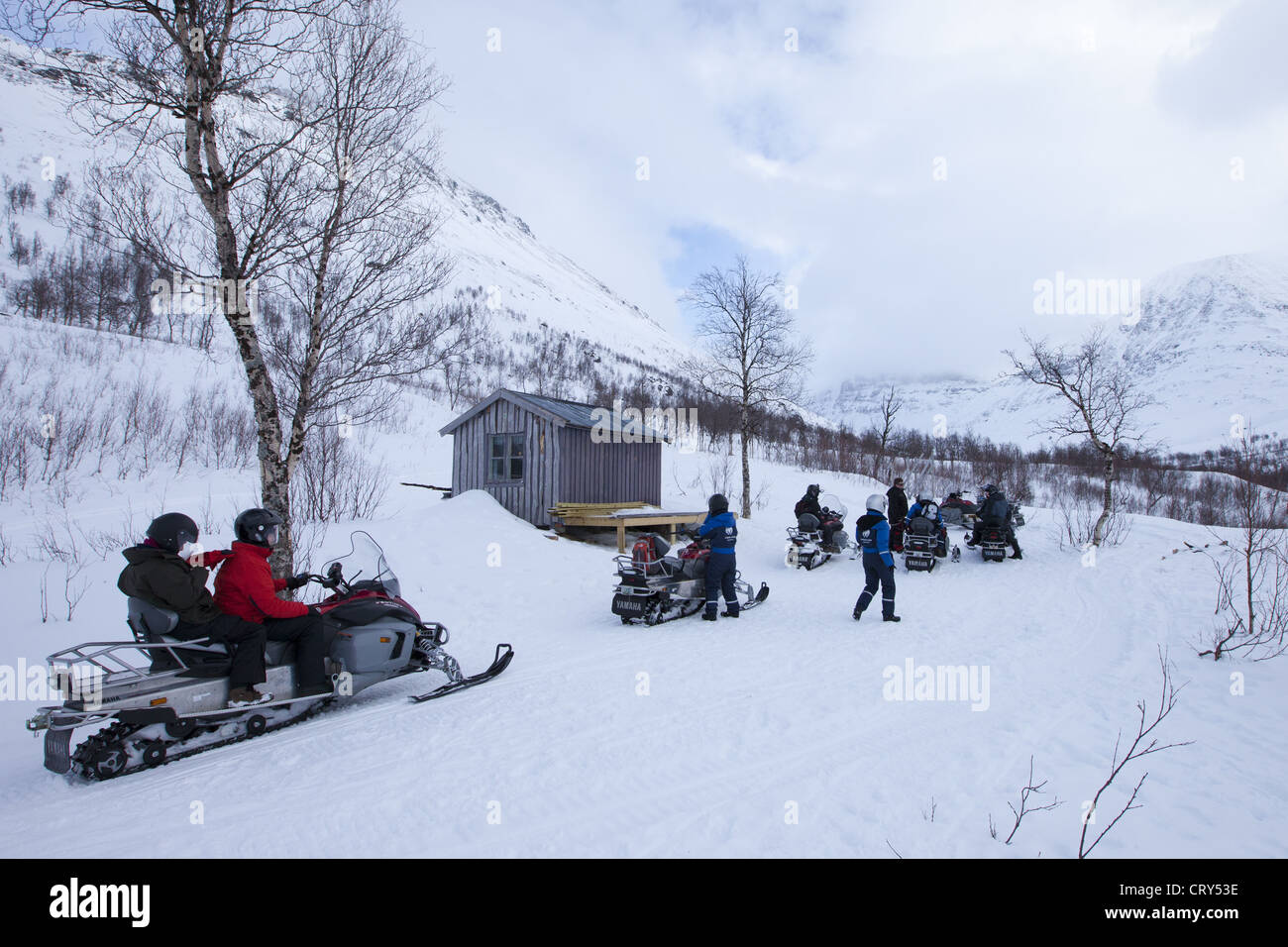 Pitstop for snowmobiling group among arctic alps in the Arctic Circle near Holt in the region of Tromso, Northern - Stock Image