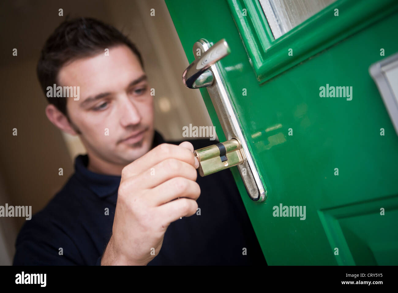 Locksmith replaces Euro cylinder lock barrel in front door - Stock Image