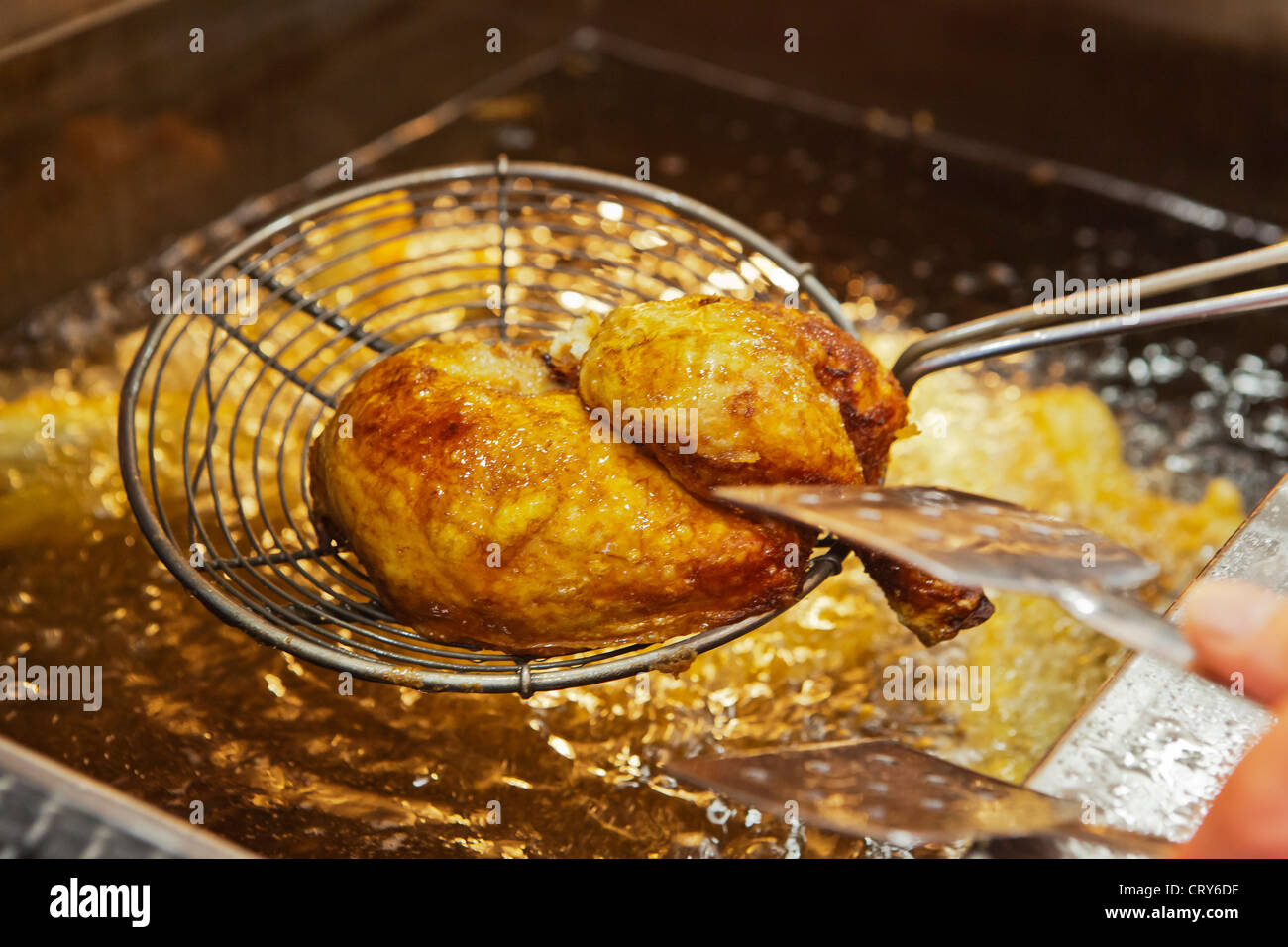 Quarter of chicken coming out of the fryer. - Stock Image