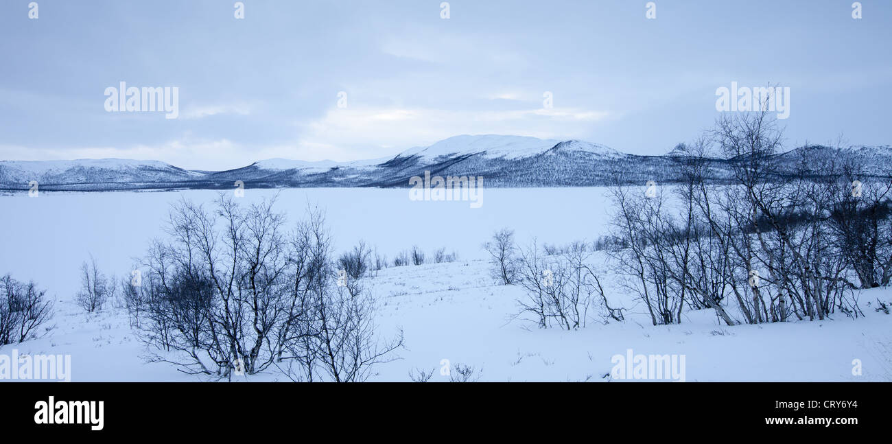 Frozen Kilpisjarvi lake with Sweden in the background in arctic wilderness at nightfall by Kilpisjarvi, Finland - Stock Image
