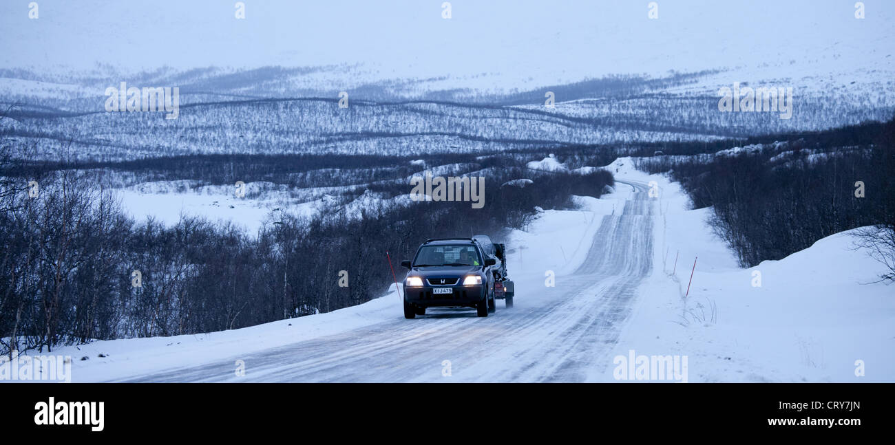 Car with trailer towing snowmobile through arctic wilderness at nightfall by Kilpisjarvi on route from Norway into - Stock Image