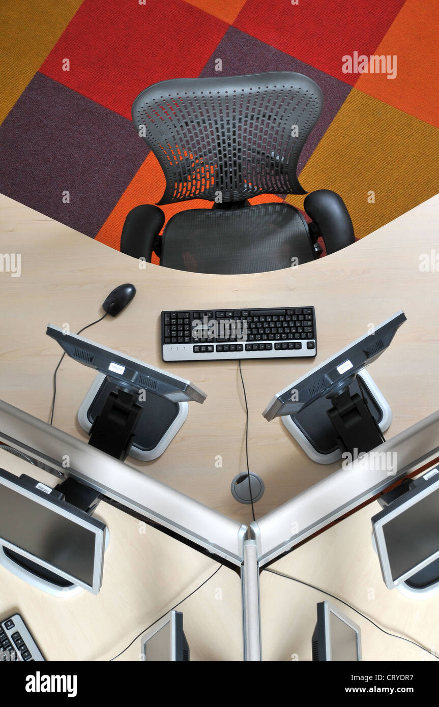 Seen from above an office hot desk with computer screens keyboards and chair Stock Photo
