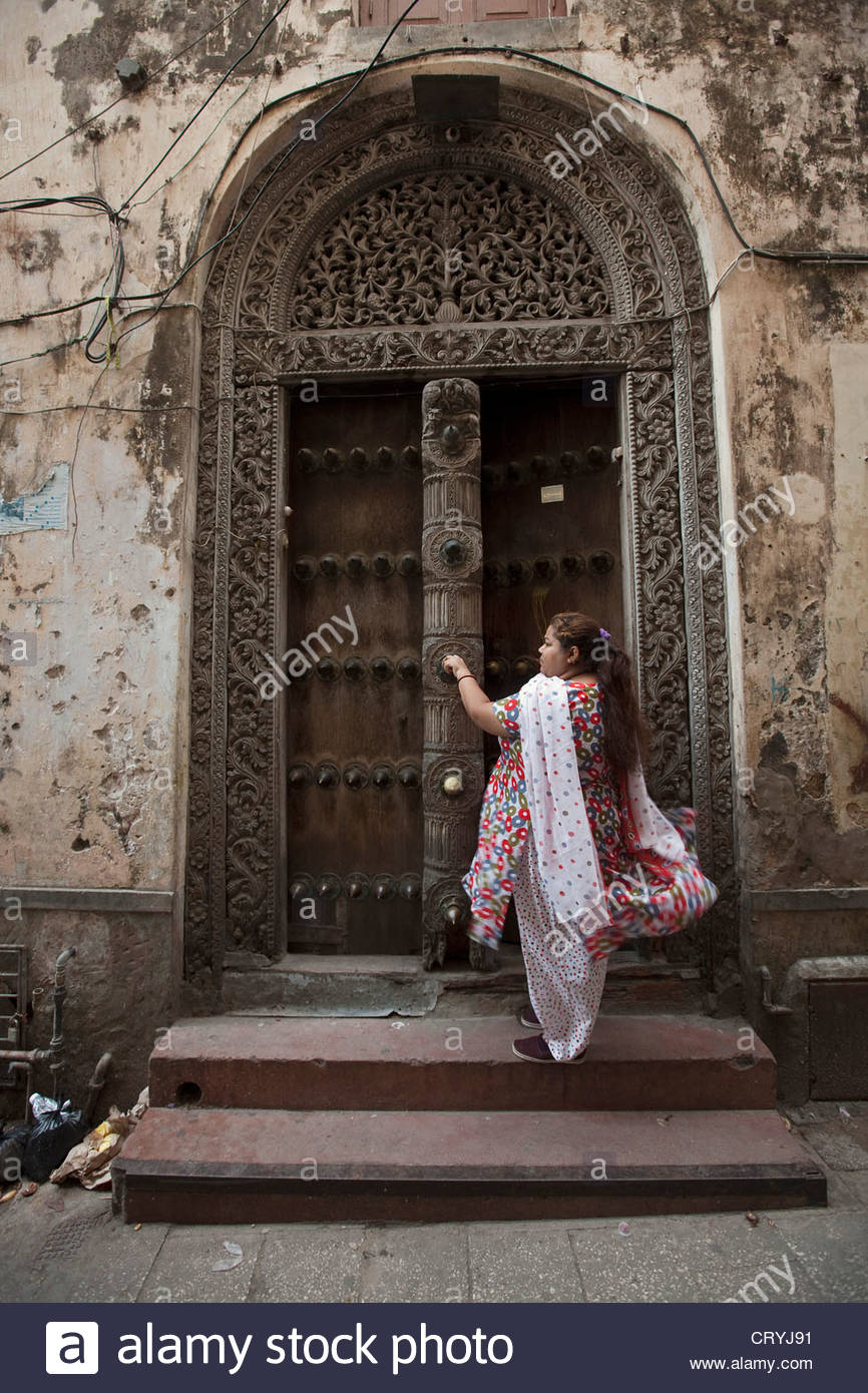 Woman in colourful traditional in front of a carved wooden doorway Stock Photo