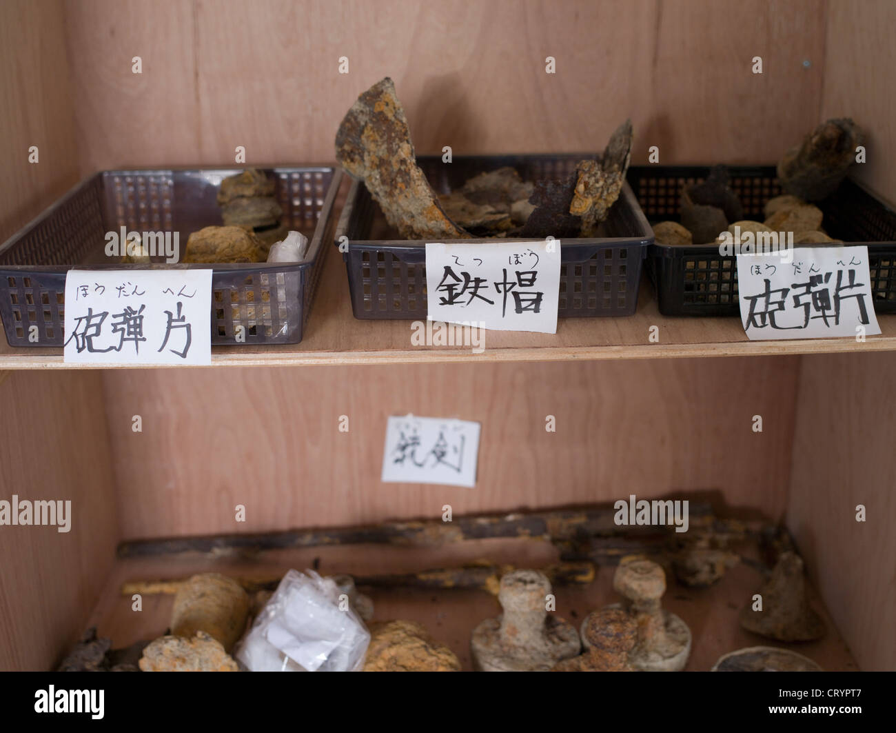 Rusting helmets, grenades and weapons from WWII that are found during construction on Okinawa - Stock Image