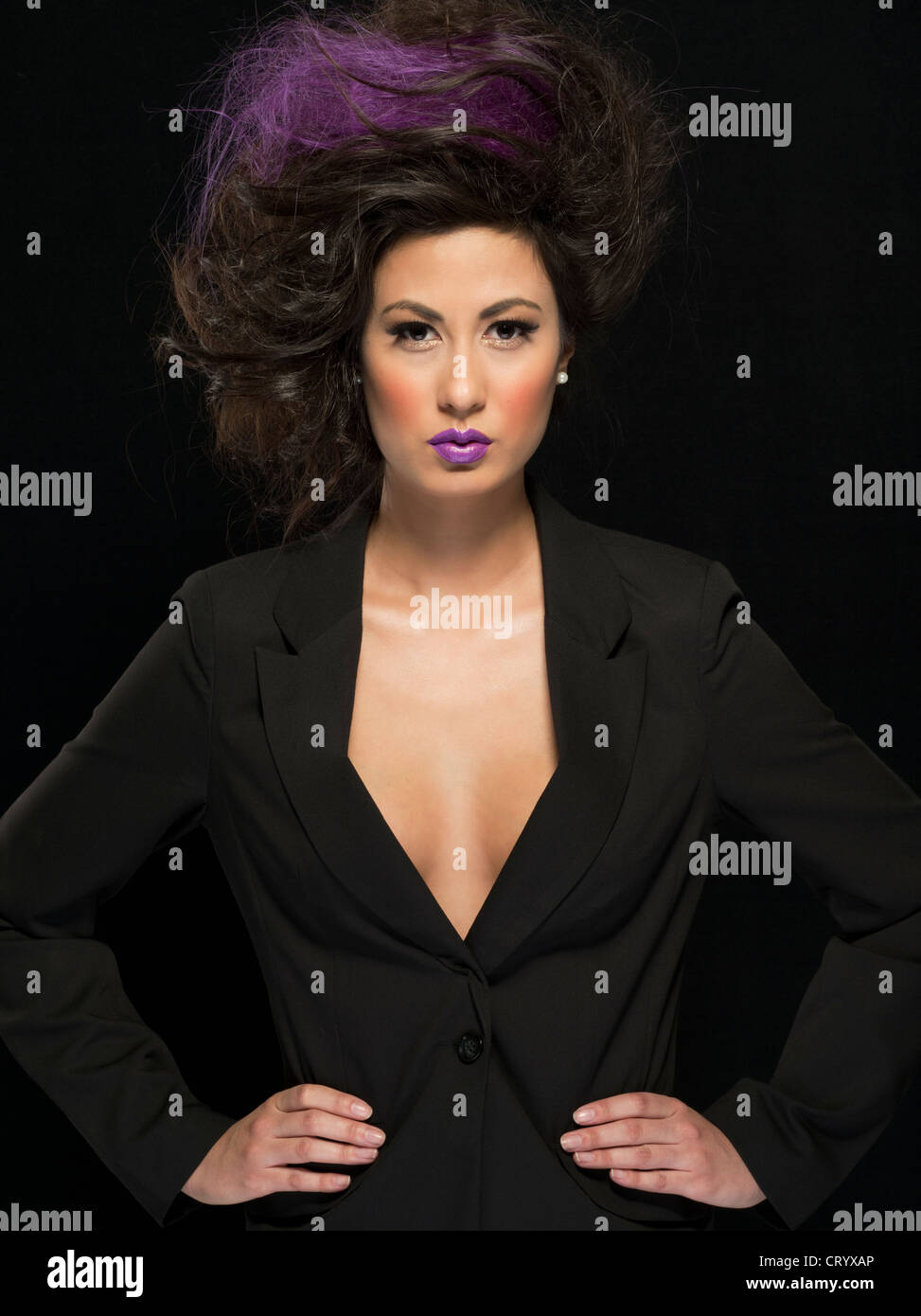 Imposing woman with black jacket hands on hips, purple tint to the hair and matching purple lipstick Stock Photo