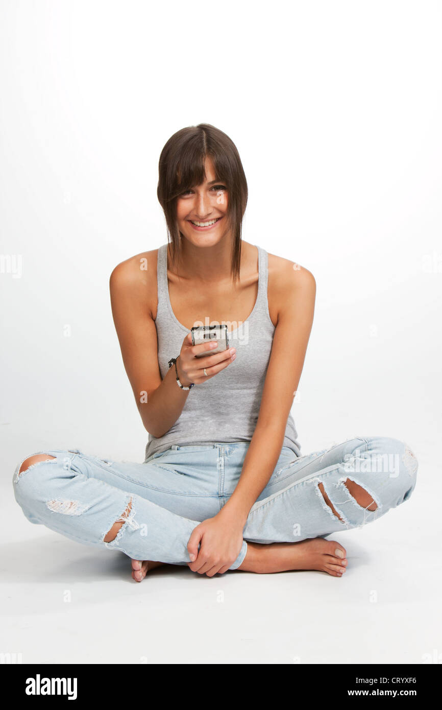 Young woman sitting cross-legged smiling tiping a smartphone - Stock Image