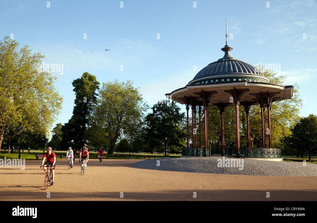 Cyclists cycling past the bandstand at sunrise, Clapham Common, London UK - Stock Image