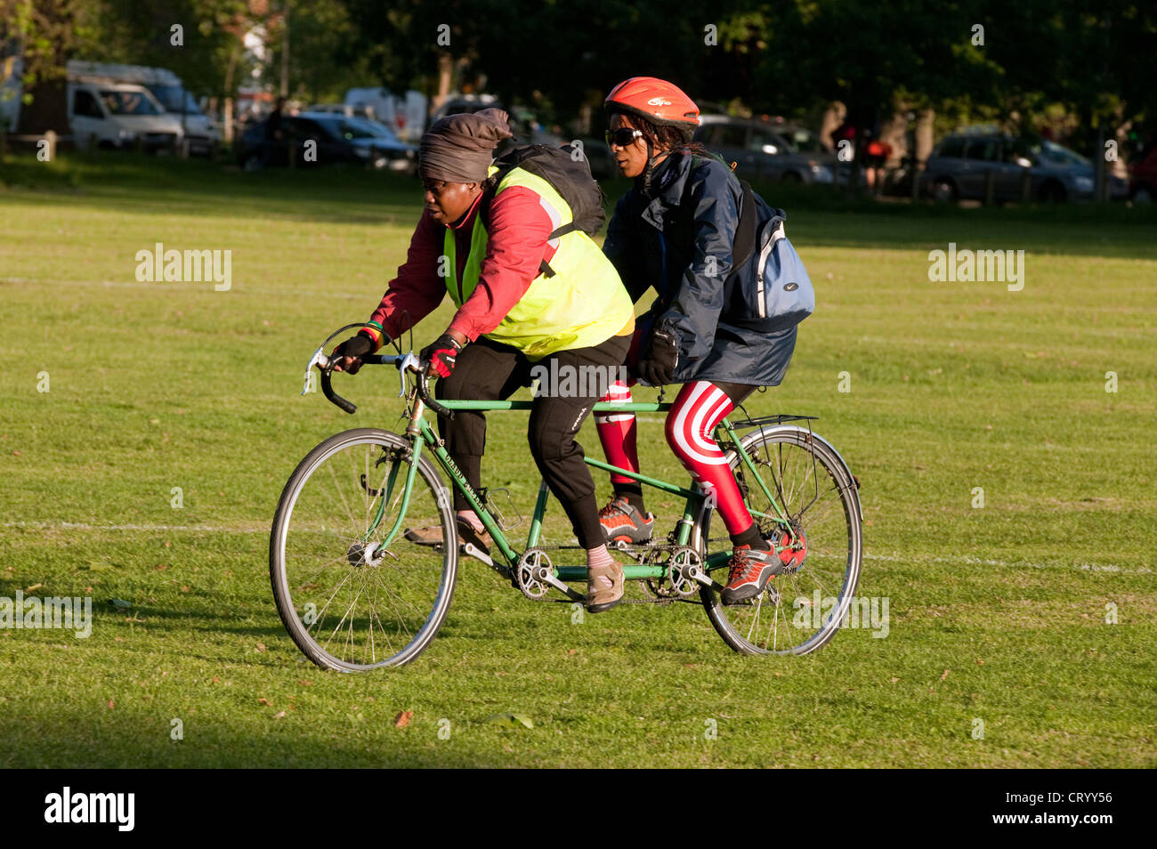 Two black women riding a tandem, Clapham Common London UK - Stock Image