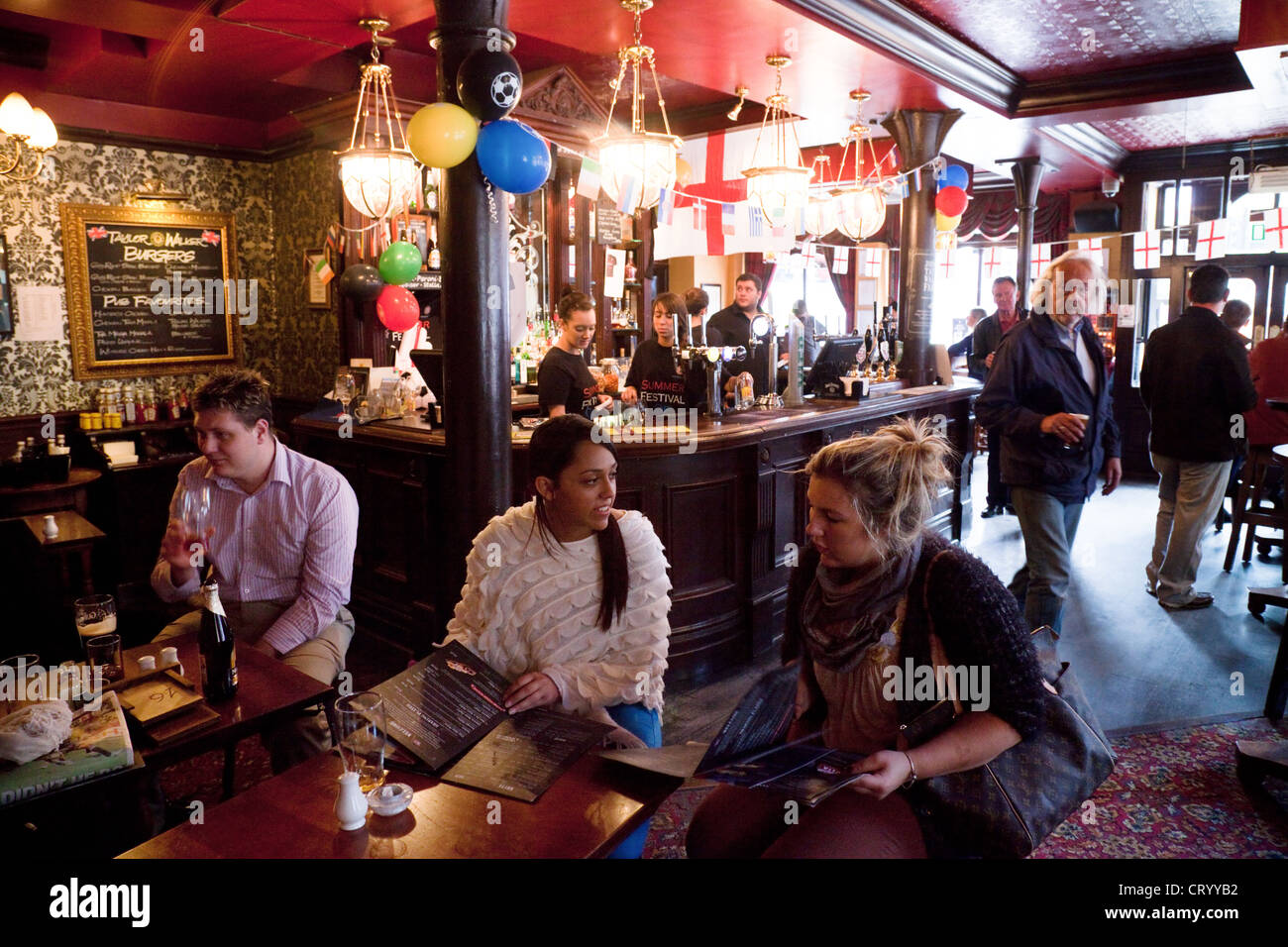 People having a drink in the Duke of York pub in Victoria, London UK - Stock Image