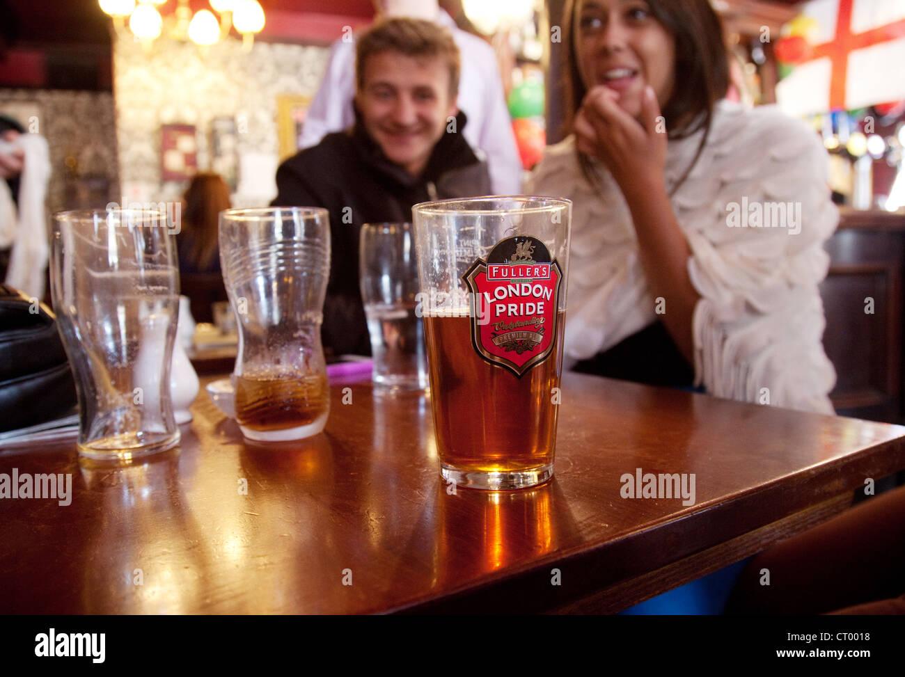 People drinking Fullers London Pride beer in the Duke of York pub, Victoria, London UK Stock Photo