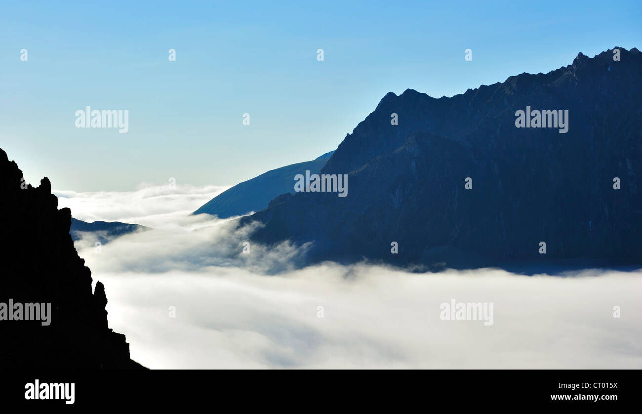 View over jagged rock edge and mountains covered in mist at sunrise, Col du Tourmalet, Hautes-Pyrénées, - Stock Image