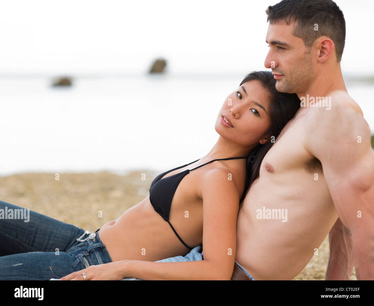 Couple on the beach and in the water on a tropical island. (Okinawa, Japan) - Stock Image
