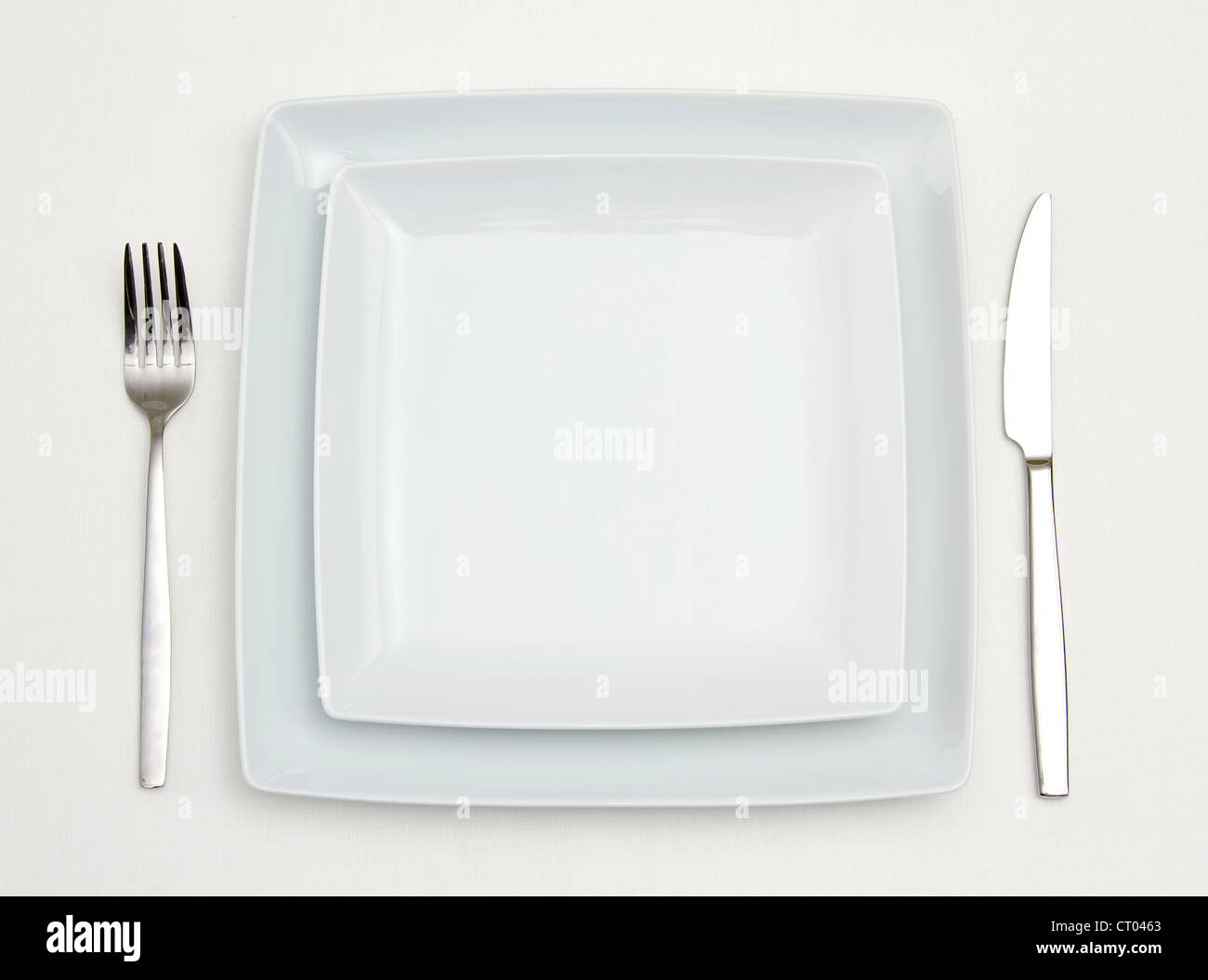 Dinner place setting. white square china plates with silver fork and knife & Dinner place setting. white square china plates with silver fork and ...