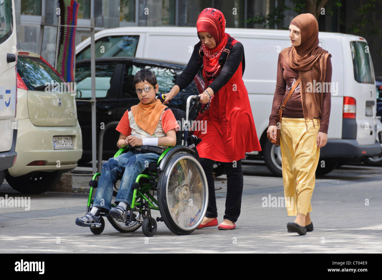 Mentally Physically Disabled Middle Eastern Teenager in Wheel Chair assisted by young women in traditional Islamic - Stock Image